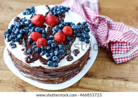 Tart with strawberries and blueberries on wood background with r