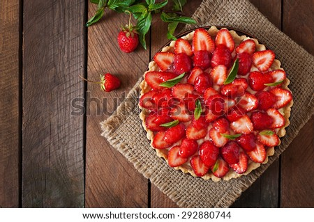 Tart with strawberries and whipped cream decorated with mint leaves. Top view - stock photo