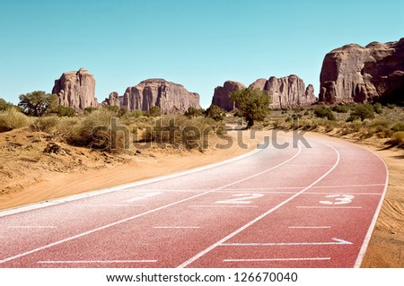 "tartan race track placed between mountains of ""Monument Valley"" - stock photo"