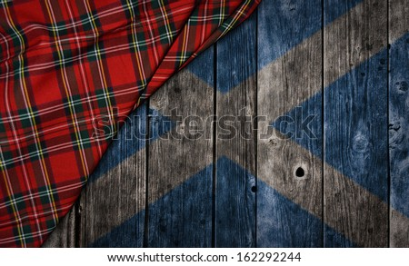tartan textile on wooden background with scotland flag - stock photo