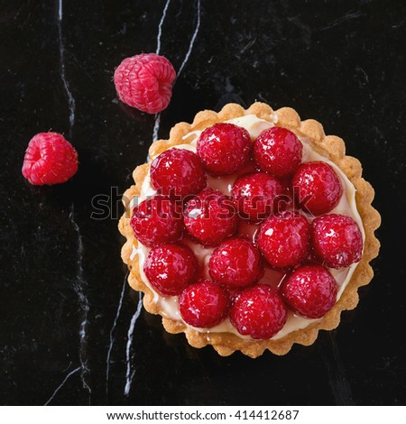 Tartlet with custard and fresh glazed raspberries, served on black marble surface. Top view. Square image