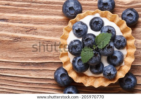 Tartlet with fresh blueberries on a wooden background horizontal view from above   - stock photo