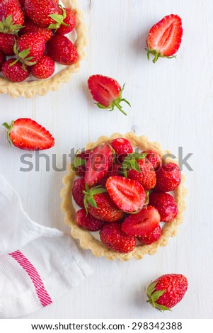 Tartlets with fresh strawberry on white wooden background, top view - stock photo