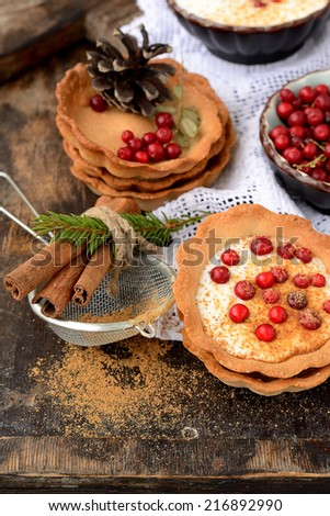 tartlets with homemade sour cream and cranberries on a wooden table with a white tablecloth in a rustic style