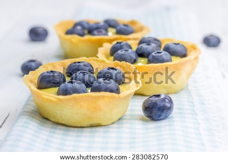 Tartlets with lemon curd and blueberries, closeup - stock photo