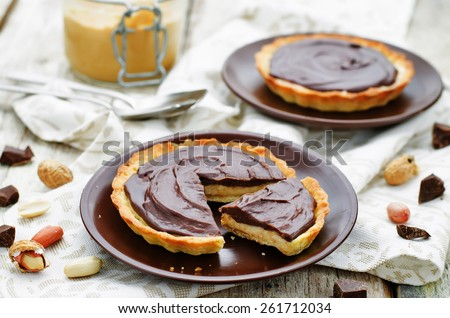 tartlets with peanut butter mousse and chocolate on a white wood background. tinting. selective focus - stock photo