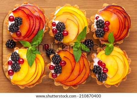 Tarts with fruits on the wooden desk - stock photo