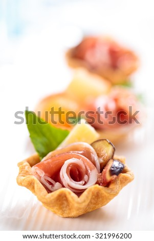 Tarts with meat, basil, melon balls and figs. Shallow dof.  Focus on parts of meat.