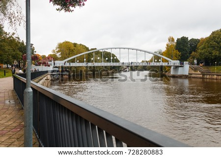 TARTU, ESTONIA - OCTOBER 5, 2017: first pedestrians cross the pedestrian bridge Kaarsild after the renovation. View from the right bank of the Emajogi river.