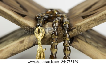 Tasbih, scripture, rosary or prayer beads on wooden bookstand for the Koran. Slightly defocused and close-up shot. - stock photo