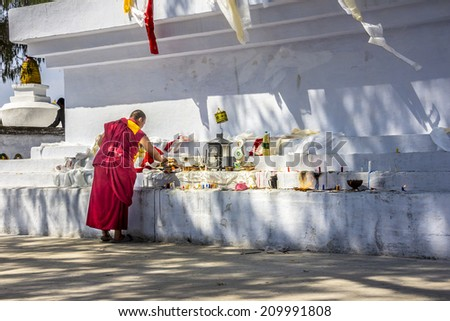TASHIDING, INDIA - MARCH 16, 2014: A monch at bumchu festival, Tashiding, Sikkim, isworshipping the buddha at a big Stupa (chorten, choerten) - stock photo