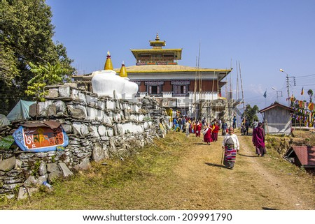 TASHIDING, INDIA - MARCH 16, 2014: People are streaming out of the temple along a mani wall. A wall, engraved with buddhist prayers. - stock photo