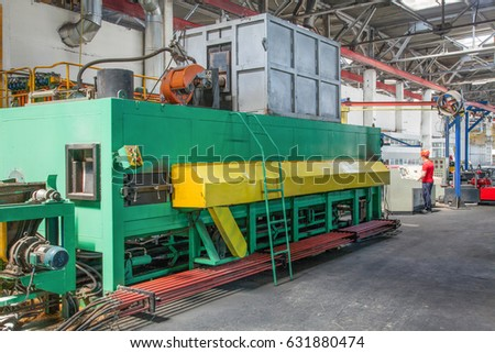 Tashkent, Uzbekistan - May 23, 2014: factory for the production of aluminum profiles. Press machine for extrusion of aluminum and worker behind the control panel.