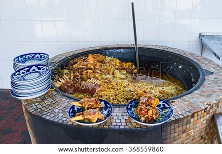 TASHKENT, UZBEKISTAN - MAY 7, 2015: The large pilaf cauldron (qozon) and plates with lamb meat in open air kitchen of Center Asian Plov Center, on May 7 in Tashkent. - stock photo