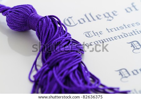 tassel/honor cords resting on top of graduation paperwork - stock photo