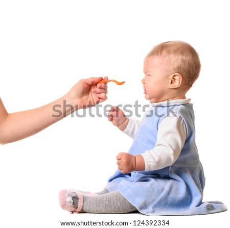tasteless. woman is feeding her baby with a spoon - stock photo