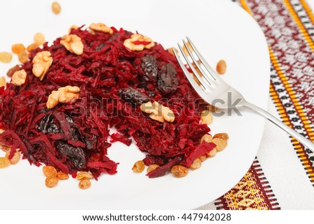 Tasting sweet salad with beets, prunes and walnuts. Fork on the plate. Low aperture shot, focus on front part of the shot - stock photo