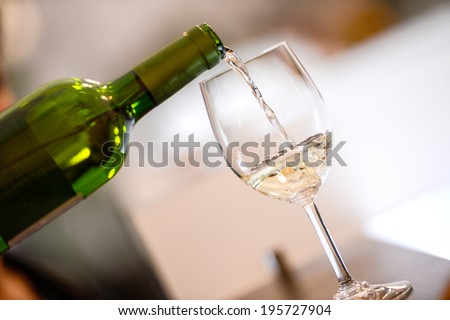 Tasting-White wine pour in a glass - stock photo