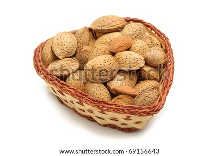 Tasty almond nuts in in wicker bowl  isolated on white