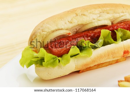 Tasty and appetizing  hot dog over wooden background