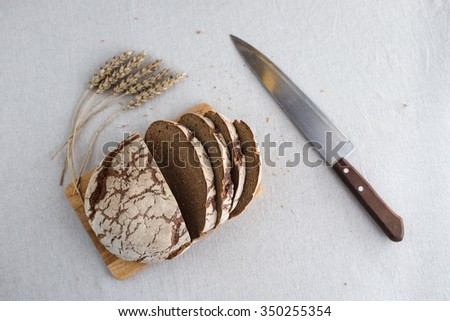 Tasty and delicious sliced loaf of bread on a board. Bread is on a background of linen fabric. Nearby lies the knife.