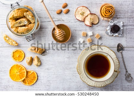 Tasty and healthy almond cookies, rich in vitamins, minerals in a glass jar, cup of tea, honey, almonds, chocolates, dried apples, dried lemons and sugar on white wooden table. copy space.Top view.