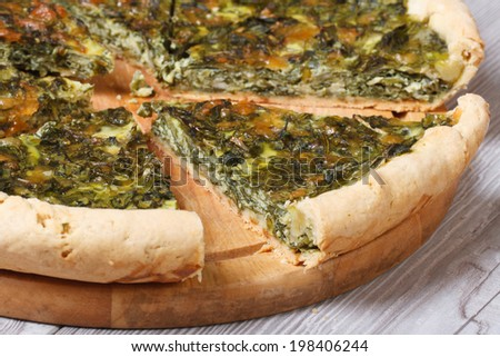 tasty and healthy chopped spinach pie with a close-up on a cutting board. horizontal.  - stock photo