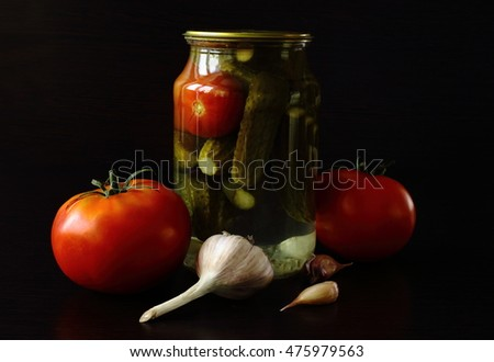 tasty and healthy food for your health cucumbers and tomatoes in a glass jar. some are fresh. dark background