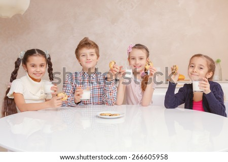 Tasty and healthy meal. Small school kids drinking milk with biscuits by the table at home and smiling at a camera - stock photo