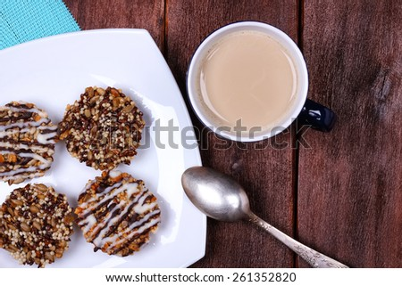 Tasty and healthy seeds cookies and a cup of latte. Coffee with milk on the table. Mug of coffee, dessert spoon and cookies on a plate. Top view. - stock photo
