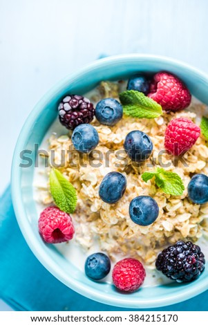 Tasty and light diet cereal breakfast with sumer fruits, fresh milk and honey. Diet concept and wellbeing. - stock photo