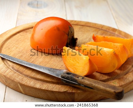 Tasty and ripe persimmon on wodden board