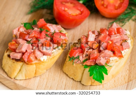 Tasty appetizer crostini (crostino) with tomato and sausage