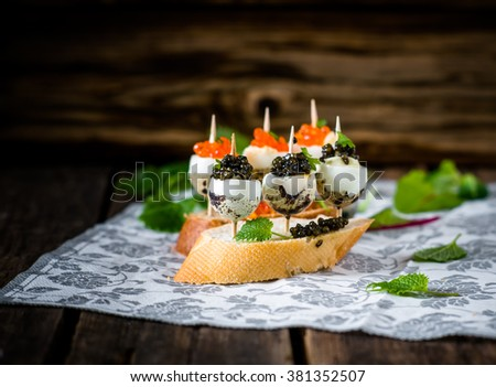 Tasty appetizer of quail eggs with red and black caviar