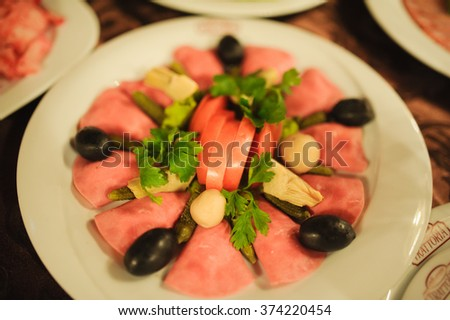 Tasty appetizer.  Plate of sausage and smoked meat or ham - stock photo