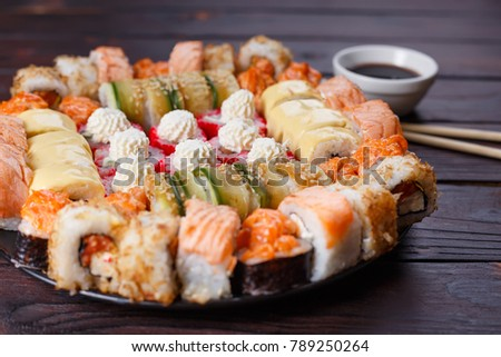 Tasty appetizing multicolored sushi rolls set, served with soy sauce and chopsticks on wooden table. Sushi restaurant menu, Japanese food, delicious seafood concept.