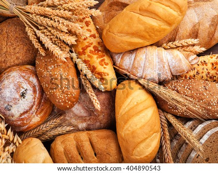 tasty assorted breads on old wooden board