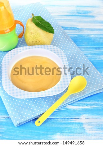 Tasty baby fruit puree and baby bottle on wooden table - stock photo
