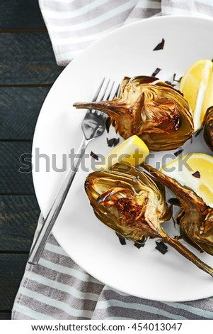 Tasty backed artichoke on a white plate, close up