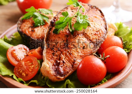 Tasty baked fish on plate on table close-up - stock photo