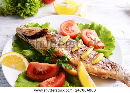 Tasty baked fish on table close-up