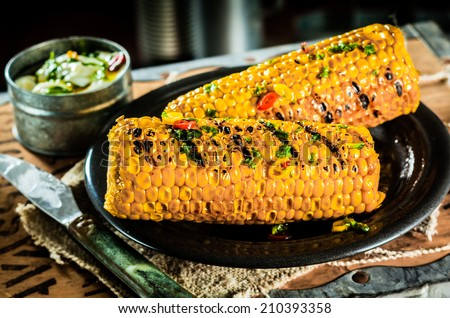 Tasty barbecued or grilled corn on the cob seasoned with spices and herbs in a rustic settingwith burlap on an old tea chest lid - stock photo
