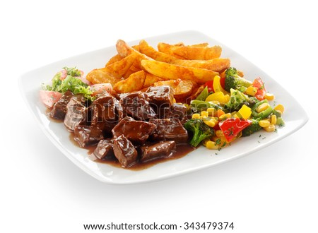 Tasty beef goulash served with mixed fresh vegetables and golden French fries on a square white plate, over white - stock photo
