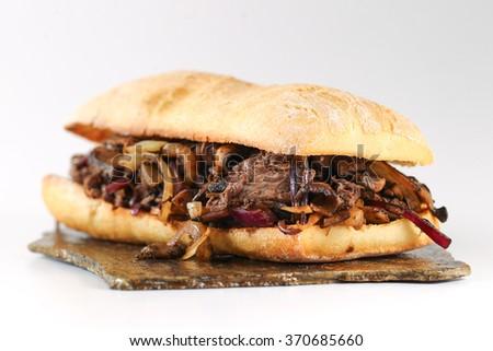 Tasty beef steak onion mushroom sandwich in a ciabatta on stone platter - stock photo