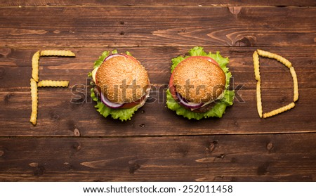 Tasty big burgers with french fries forming word food on wooden background
