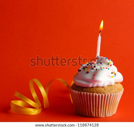 tasty birthday cupcake with candle, on red background - stock photo