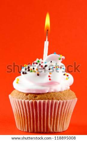 tasty birthday cupcake with candle, on red background