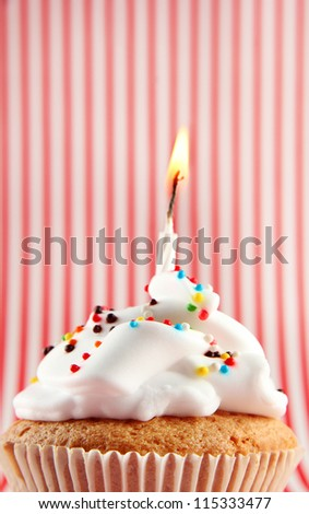 tasty birthday cupcake with candle, on red-white striped background
