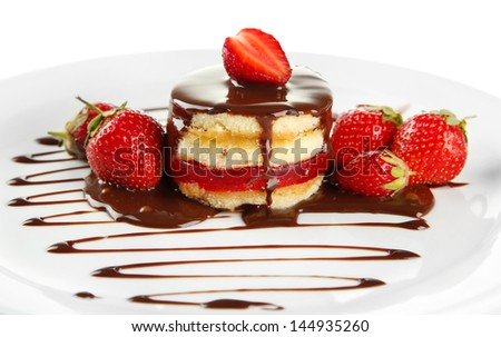 Tasty biscuit cake with chocolate and berries on plate, isolated on white - stock photo