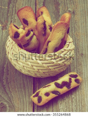 Tasty Biscuit Raisin Cookies in Wicker Bowl closeup on Rustic Wooden background. Retro Styled - stock photo
